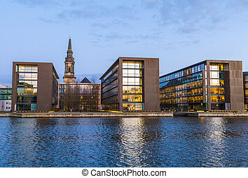Evening view of Copenhagen embankment with modern buildings and medieval Christian's church tower