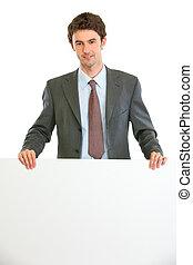 Modern business man showing blank billboard