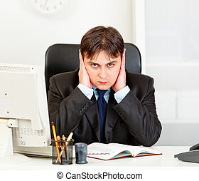 Modern business man sitting at office desk and making hear no evil gesture