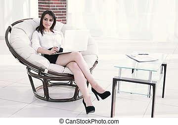 modern business woman with laptop sitting in a comfortable chair.