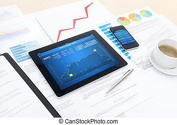 Modern business workplace with stock market data on a digital tablet, mobile banking on a smartphone and many charts and graphs on a desktop.