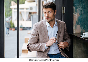 Modern businessman drinking coffee in cafe