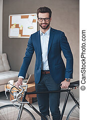 Modern businessman. Handsome young man wearing glasses and suit looking at camera with smile while standing with retro bicycle in office