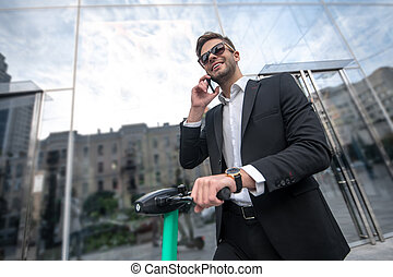 Man on a scooter in sunglasses talking on the phone