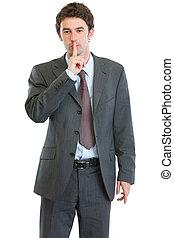 Modern businessman showing shh gesture