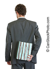 Modern businessman standing back to camera and holding gift box