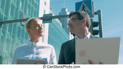 Modern businesspeople working while walking in the city