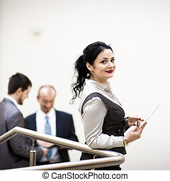 modern businesswoman holding tablet computer with colleague on background