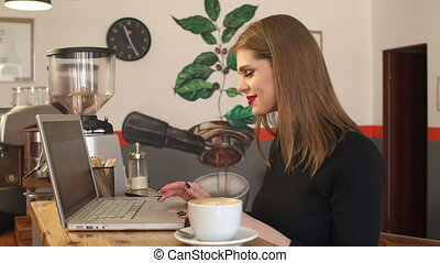 Modern businesswoman working on laptop computer at coffee shop and drink coffee