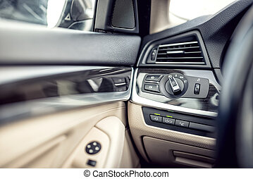 Modern car interior with leather and premium details. Headlights adjustment control and cockpit details