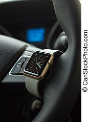 Modern car interior with smart watch on steering wheel
