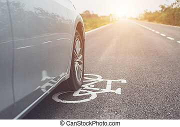 Modern car running on asphalt road / bicycle lane and tread on white bicycle sign