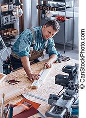 Modern carpenter measuring wood plank
