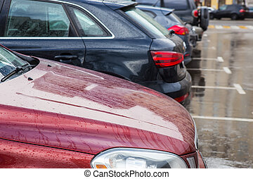 Modern cars are parked in a parking lot in row.