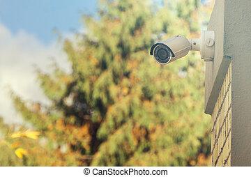 Modern CCTV camera on building wall, foliage background