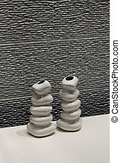 Modern ceramic vases used as room decoration near ceramic stone wall