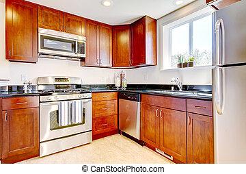 Modern cherry kitchen with steal appliances.
