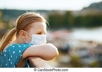 Life during coronavirus pandemic. modern child in blue overall with medical mask looking into the distance outdoors in the city.
