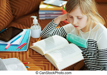 modern child with mask and reading at modern home in sunny day