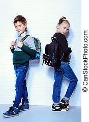 Children's fashion. Modern boy and girl posing together at studio. Education.