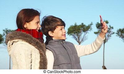 Modern children make selfies on the phone