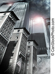 Architectural city scape of smaller brick buildings and American flag leading up to a focul point on the tops of steel reflective skyscrapers