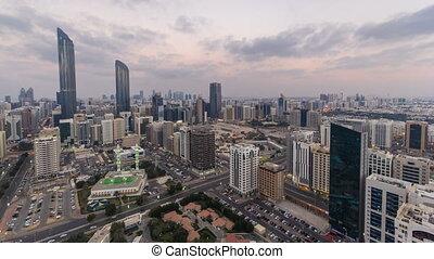 Modern city architecture of Abu Dhabi skyline day to night timelapse, UAE.