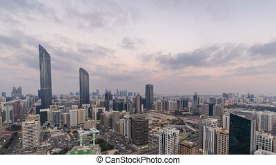 Modern city architecture of Abu Dhabi skyline day to night timelapse, UAE.