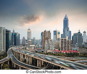 modern city skyline with elevated road junction and interchange overpass in shanghai at dusk