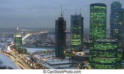 Modern city: skyscrapers, movement on highway. Gradually darkens. Time lapse.