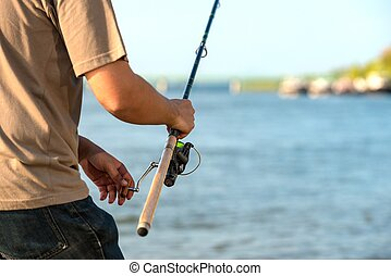 Modern clean fishing rod in hands ourdoors