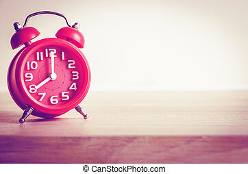 modern clock on wood table with flower pot , vintage process