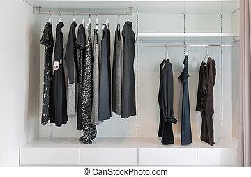 modern closet with row of black dress hanging on coat hanger in wardrobe.