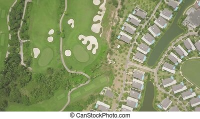 Modern cottage village with luxury houses and golf courses view from above flying drone. Aerial landscape tourist resort villa on green golf field background.