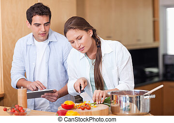 Modern couple using a tablet computer to cook