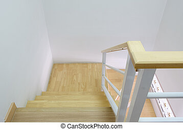 Modern curved wooden staircase with the white metal handrail.