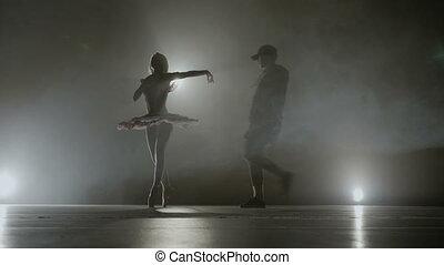 Modern dance battle between a young hip hop dancer versus a...