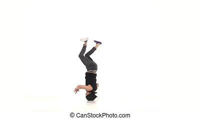 Modern dancer dancing brake-dance on head, white, slow...