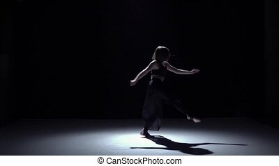 Modern dancer girl in dark dress dancing contemporary on black, shadow, slow motion