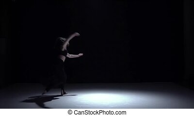 Modern dancer girl in dark dress starts dancing contemporary on black, shadow, slow motion