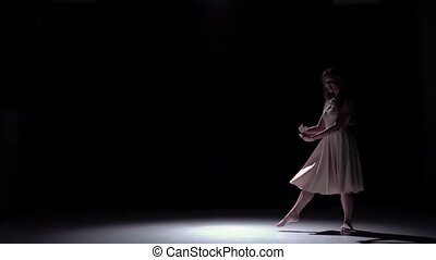 Modern dancer girl in white continues dancing contemporary, whirls on black, shadow, slow motion