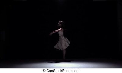 Modern dancer girl in white starts dancing contemporary, whirls on black, shadow, slow motion