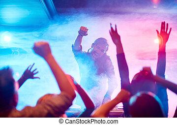 Modern dancing - Excited deejay encouraging dancing crowd in...