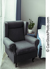 modern dark upholstered armchair in traditional light bedroom