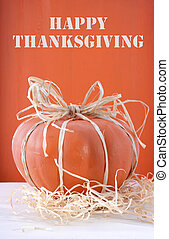 Modern painted pumpkin centerpiece decorated with rafia and straw on white wood table and orange wood background for Thanksgivng, Halloween and Autumn Fall festivities.