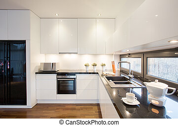 Modern designed kitchen with black fridge and white units