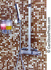 Modern designer tap and shower in bathroom.