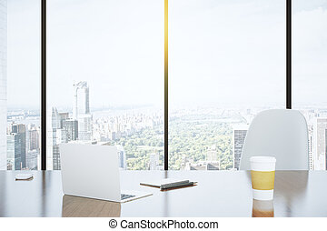 Modern desk in an office with a window and a view of the city