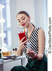 Joyful young woman holding her red smartphone