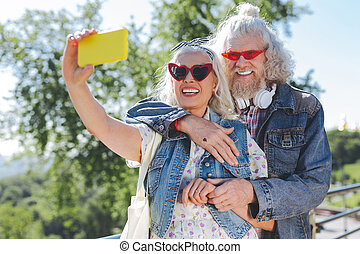 Nice cheerful woman holding her smartphone